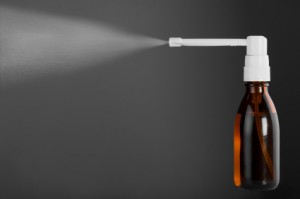 Bottle of throat spray isolated on gray background